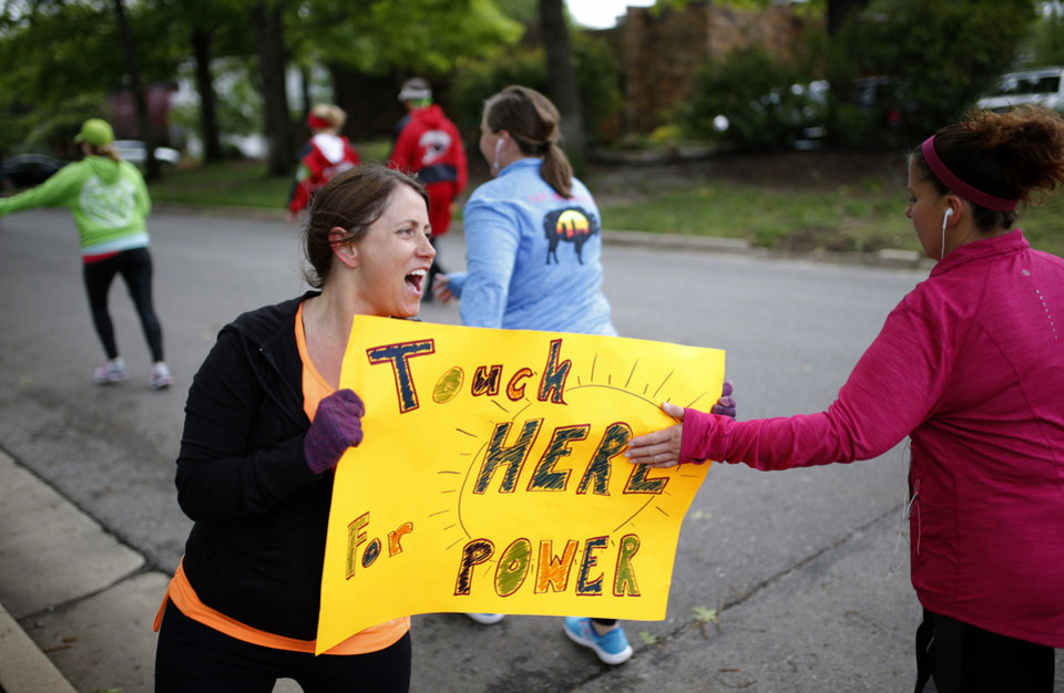 Photo - Tammy Streeter greets runners near NW 14th and Shartel Ave. during the 2017 Oklahoma City Memorial Marathon Sunday, April 30, 2017.  Photo by Sarah Phipps, The Oklahoman