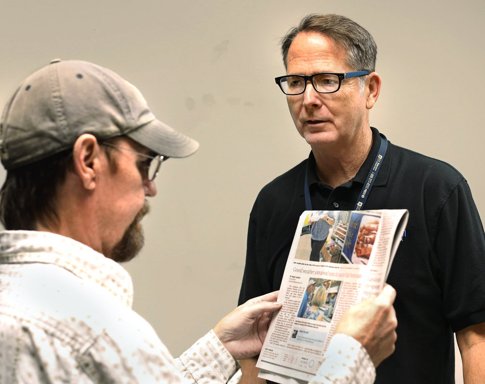 Photo -  Anthony Kirksey, right, visual impairment services team coordinator with VA Health Care System, assists a veteran with selecting a new pair of reading glasses at the Sooner Stand Down for homeless veterans on Friday. [Photo by Jim Beckel, The Oklahoman]