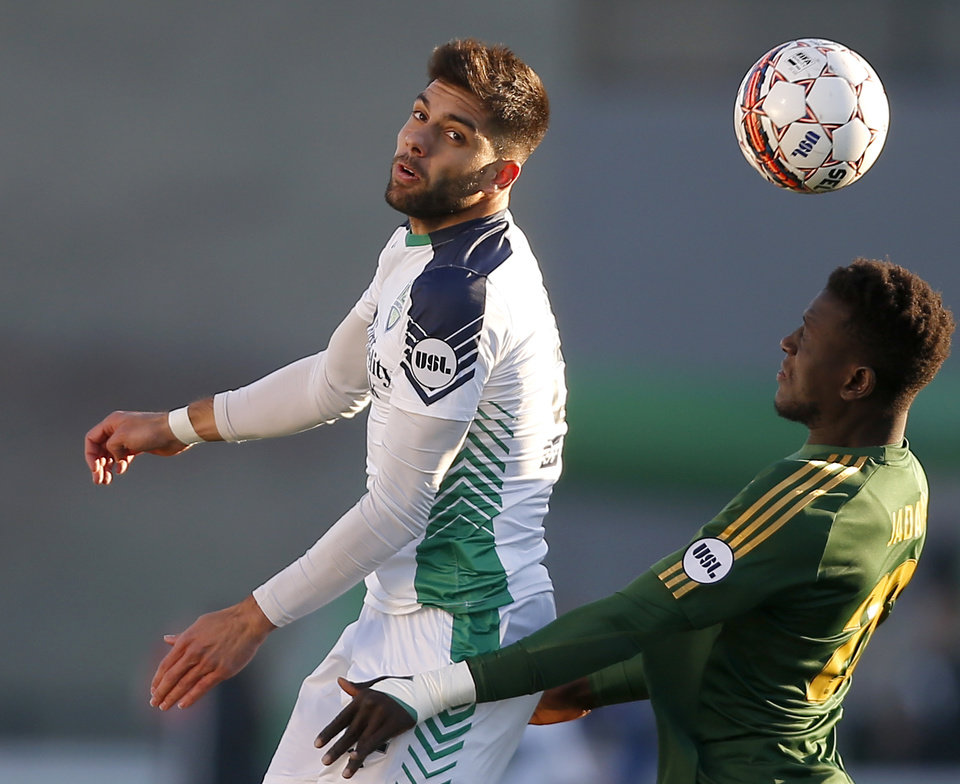 Photo -  Energy FC's Jaime Siaj, left, goes for the ball beside Portland's Modou Jadama during Saturday's match at Taft Stadium in Oklahoma City. [Photo by Bryan Terry, The Oklahoman]