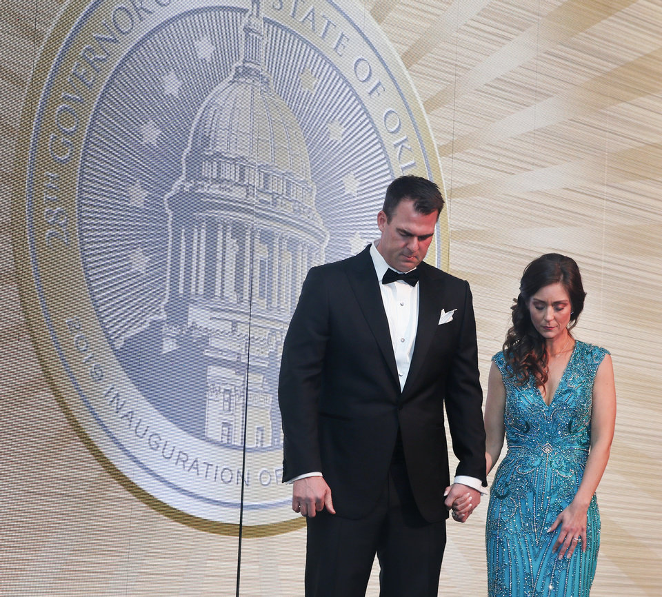 Photo - Gov. Kevin Stitt and first lady Sarah Stitt pray during the inaugural ball for Stitt at the Cox Convention Center in Oklahoma City, Monday, Jan. 14, 2019. [Nate Billings/The Oklahoman]