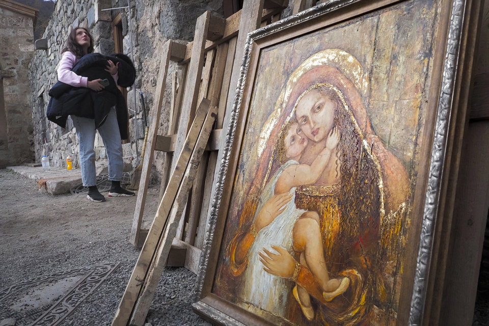 Photo -  A woman holds her baby covered with her coat next to an icon at the Dadivank, an Armenian Apostolic Church monastery dating to the 9th century, as ethnic Armenians leave the separatist region of Nagorno-Karabakh to Armenia, Saturday, Nov. 14, 2020. The territory is to be turned over to Azerbaijan on Sunday as part of territorial concessions in an agreement to end six weeks of intense fighting with Armenian forces. Hundreds of thousands of Azeris were displaced by the war that ended in 1994. It is unclear when any civilians might try to settle in Karvachar — which will now be known by its Azeri name Kalbajar — or elsewhere. (AP Photo/Dmitry Lovetsky)