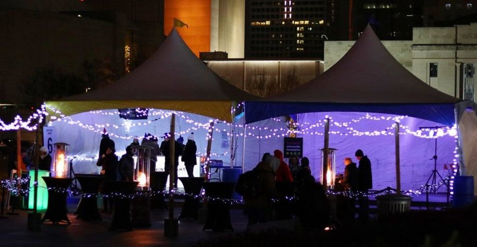 Photo - Attendees gather in the New Year's Cheers beverage tent to toast the New Year at Opening Night 2019 in Bicentennial Park in downtown Oklahoma City, Monday, December 31, 2018. [Doug Hoke/The Oklahoman Archives]