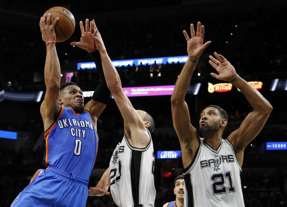 Photo - Oklahoma City's Russell Westbrook (0) shoots over San Antonio's Manu Ginobili (20) and Tim Duncan (21) during Game 2 of the second-round series between the Oklahoma City Thunder and the San Antonio Spurs in the NBA playoffs at the AT&T Center in San Antonio, Monday, May 2, 2016. Photo by Bryan Terry, The Oklahoman