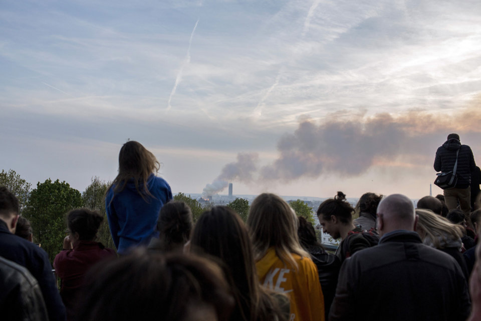 Photo - People watch Notre Dame cathedral burning in Paris, Monday, April 15, 2019. Massive plumes of yellow brown smoke is filling the air above Notre Dame Cathedral and ash is falling on tourists and others around the island that marks the center of Paris. (AP Photo/Rafael Yaghobzadeh)