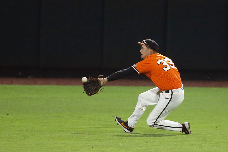 Photo - Oklahoma State's Trevor Boone (33) catches the ball for an out in the first inning of a Big 12 baseball tournament game between Oklahoma State University (OSU) and TCU at Chickasaw Bricktown Ballpark in Oklahoma City, Okla., Wednesday, May 22, 2019.  [Bryan Terry/The Oklahoman]
