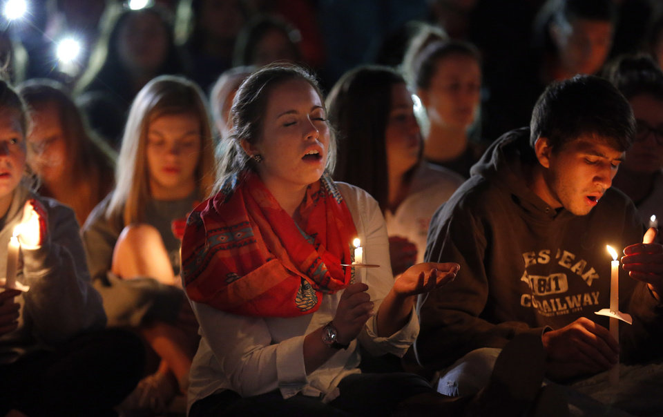 Photo - Students sing in  prayer during a candle light vigil on the campus of Oklahoma State University,  Sunday, Oct. 25, 2015. The community gathered on the campus to remember those affected by the homecoming fatality crash. Photo by Sarah Phipps, The Oklahoman