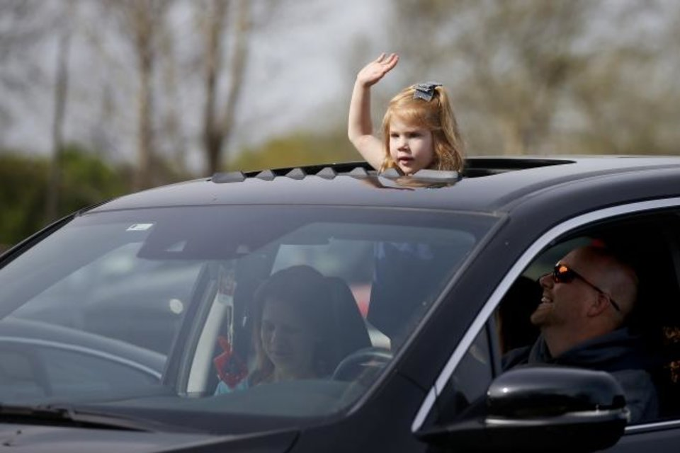 Photo -  Analyn Madewell, 4, stands between her parents, Sam and Debra Madewell, in the family's vehicle during a