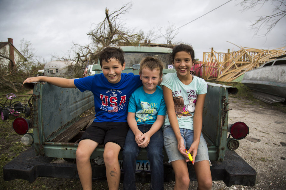 Photo - Kyler Carpenter, from left, Cory Carpenter and Laela Carpenter sit in the back of a truck in front of Laela's home in Bayside, Texas, on Saturday, Aug. 27, 2017, near damage from Hurricane Harvey. (Olivia Vanni/The Victoria Advocate via AP)