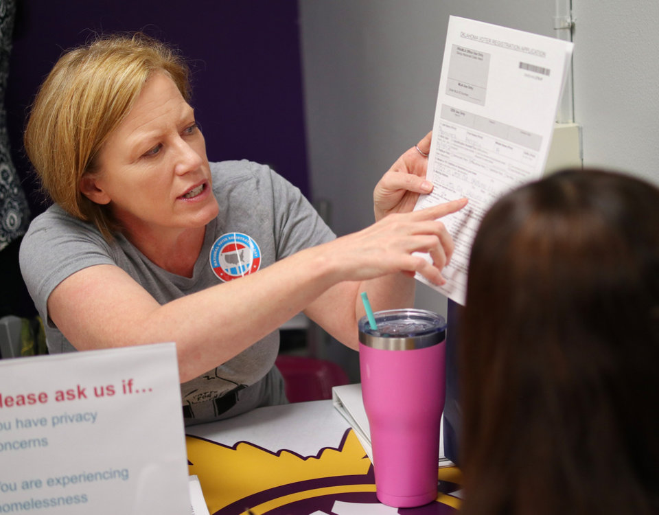 Photo - April Mays explains a section to  Magaly Ramirez, 17. Generation Citizen set up at Northwest Classen High School during lunch to register students age 17 and older to vote, Wednesday, September 25, 2019. [Doug Hoke/The Oklahoman]