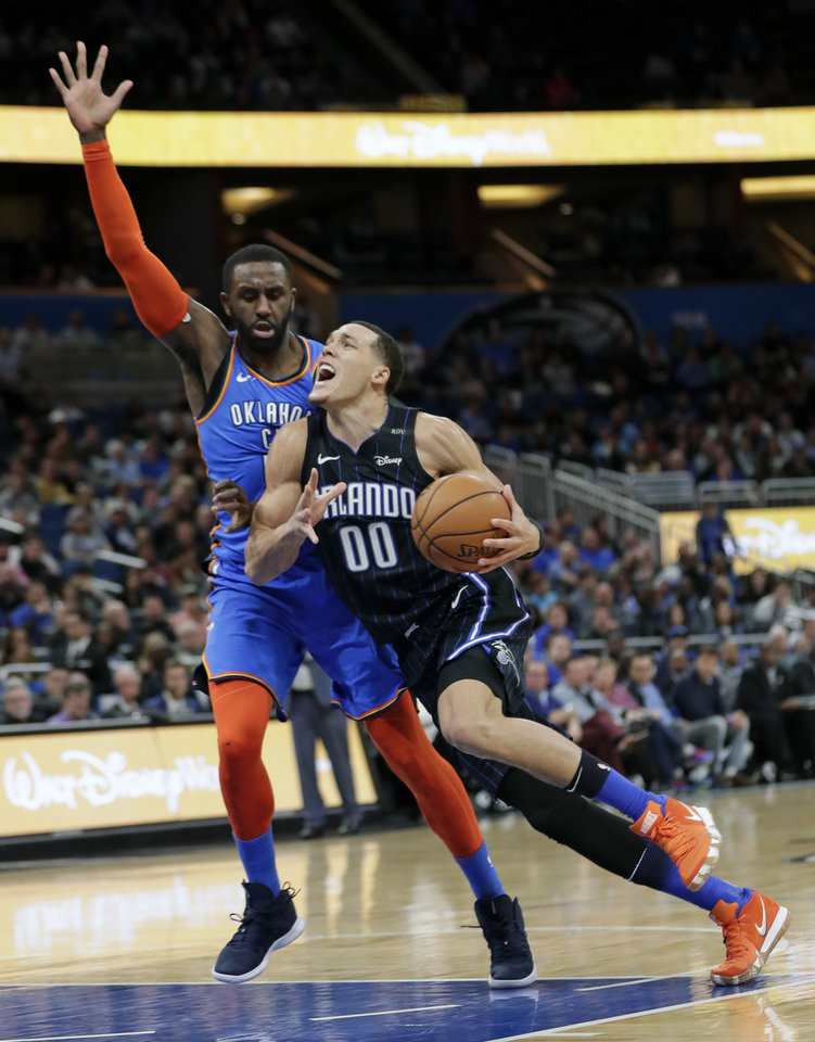 Photo - Orlando Magic's Aaron Gordon (00) goes past Oklahoma City Thunder's Patrick Patterson, left, for a basket during the second half of an NBA basketball game, Tuesday, Jan. 29, 2019, in Orlando, Fla. (AP Photo/John Raoux)