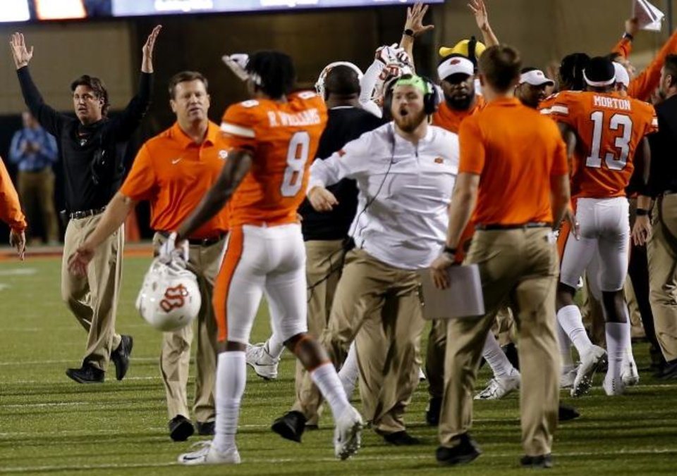 Photo -  Oklahoma State coach Mike Gundy, left, celebrates at the end of last season's 38-35 win against Texas at Boone Pickens Stadium in Stillwater. [Sarah Phipps/The Oklahoman]