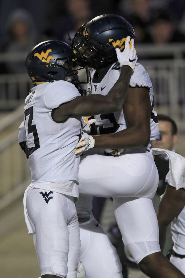 Photo - West Virginia wide receiver Sam James (13) congratulates fellow wide receiver Bryce Wheaton (83) after a touchdown during the second half of an NCAA college football game against Kansas State in Manhattan, Kan., Saturday, Nov. 16, 2019. (AP Photo/Orlin Wagner)