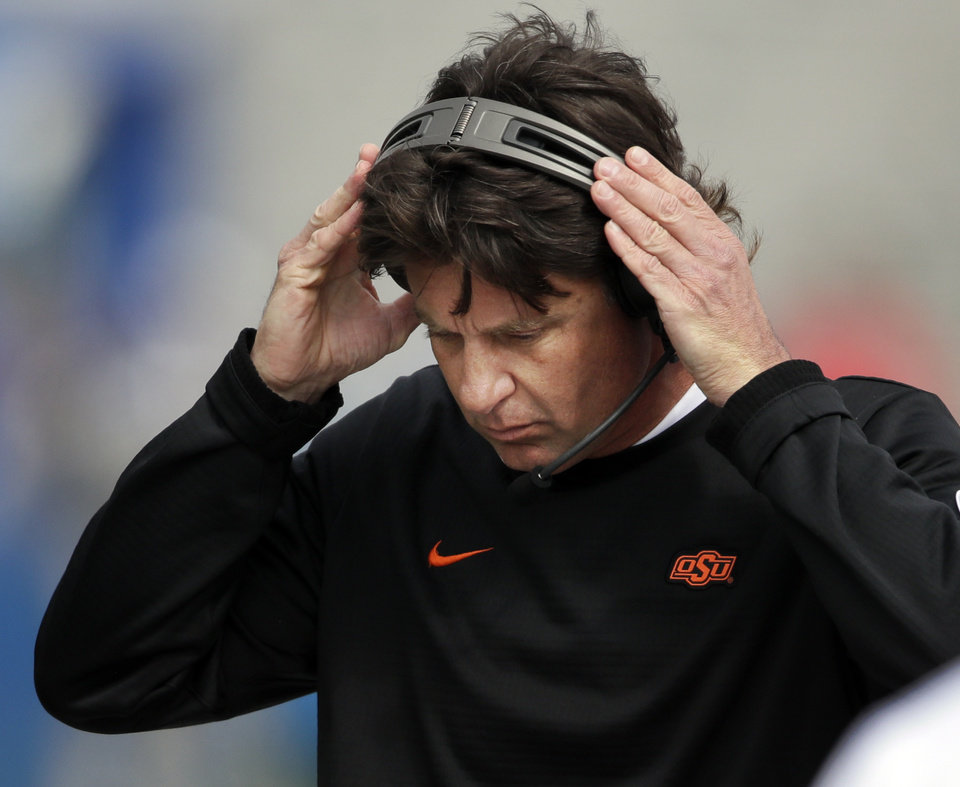 Photo - Oklahoma State head coach Mike Gundy adjusts his headset during the first half of an NCAA college football game against Kansas in Lawrence, Kan., Saturday, Sept. 29, 2018. (AP Photo/Orlin Wagner)