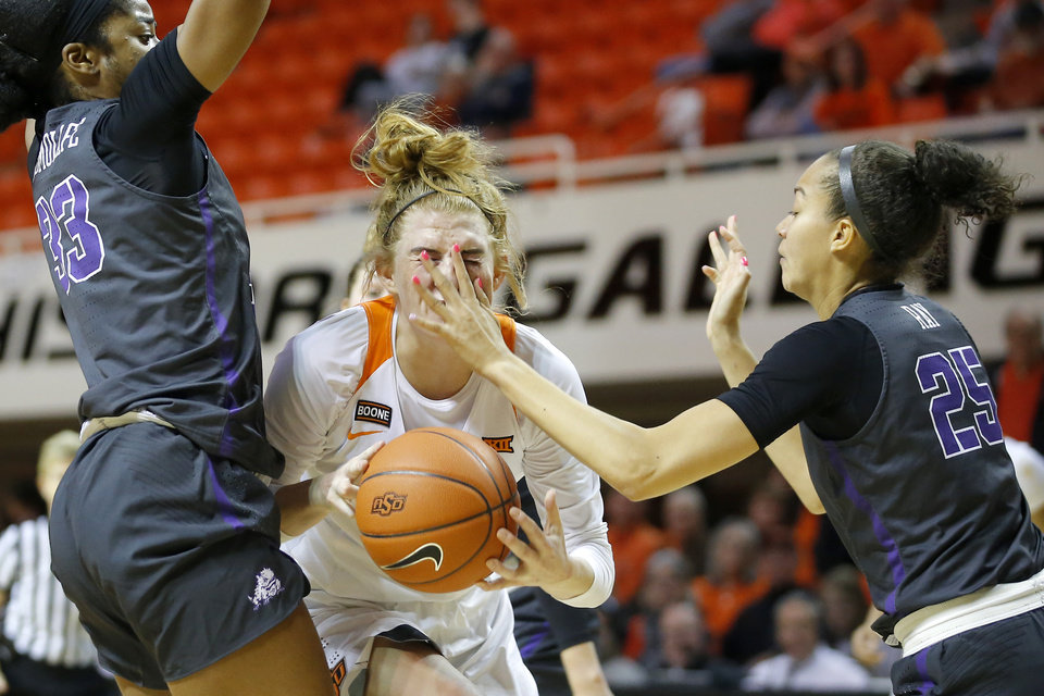 Photo - Oklahoma State's Vivian Gray (12) is hit by TCU's Kianna Ray (25) as she goes past Adeola Akomolafe (33) during a women's NCAA basketball game between the Oklahoma State University Cowgirls (OSU) and the TCU Horned Frogs at Gallagher-Iba Arena in Stillwater, Okla., Wednesday, Jan. 29, 2020. Oklahoma State lost 72-68. [Bryan Terry/The Oklahoman]