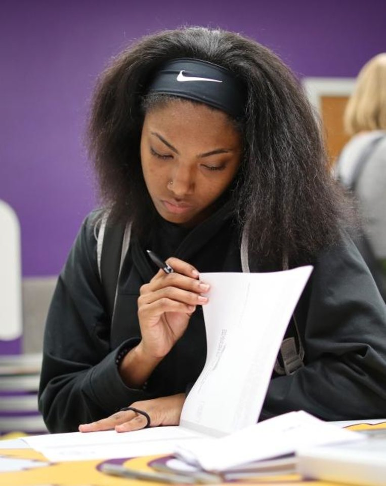 Photo -  Takare Brennon, 17, fills out voter registration form. [Doug Hoke/The Oklahoman]