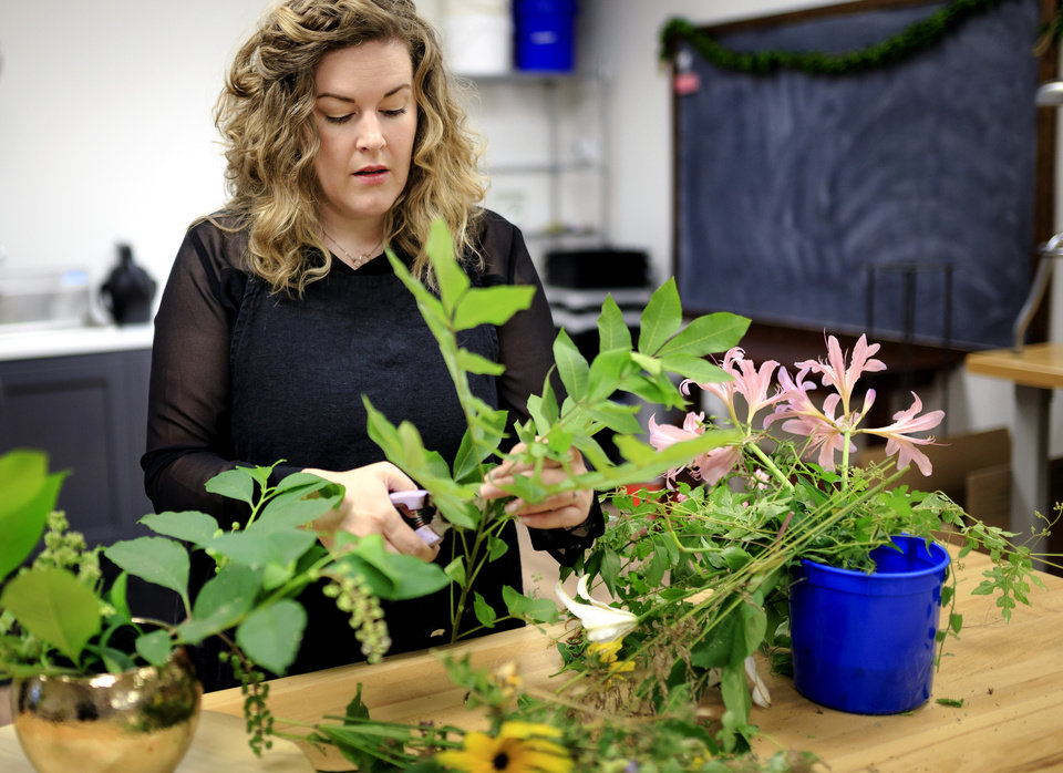 Photo -  Juniper Designs owner and floral designer Alison Fleck works on an arrangement at her studio in Oklahoma City. [Photo by Chris Landsberger, The Oklahoman]