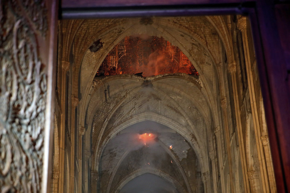 Photo - Flames and smoke are seen as the interior at Notre Dame cathedral in Paris, Monday, April 15, 2019. A catastrophic fire engulfed the upper reaches of Paris' soaring Notre Dame Cathedral as it was undergoing renovations Monday, threatening one of the greatest architectural treasures of the Western world as tourists and Parisians looked on aghast from the streets below. (Philippe Wojazer/Pool via AP)