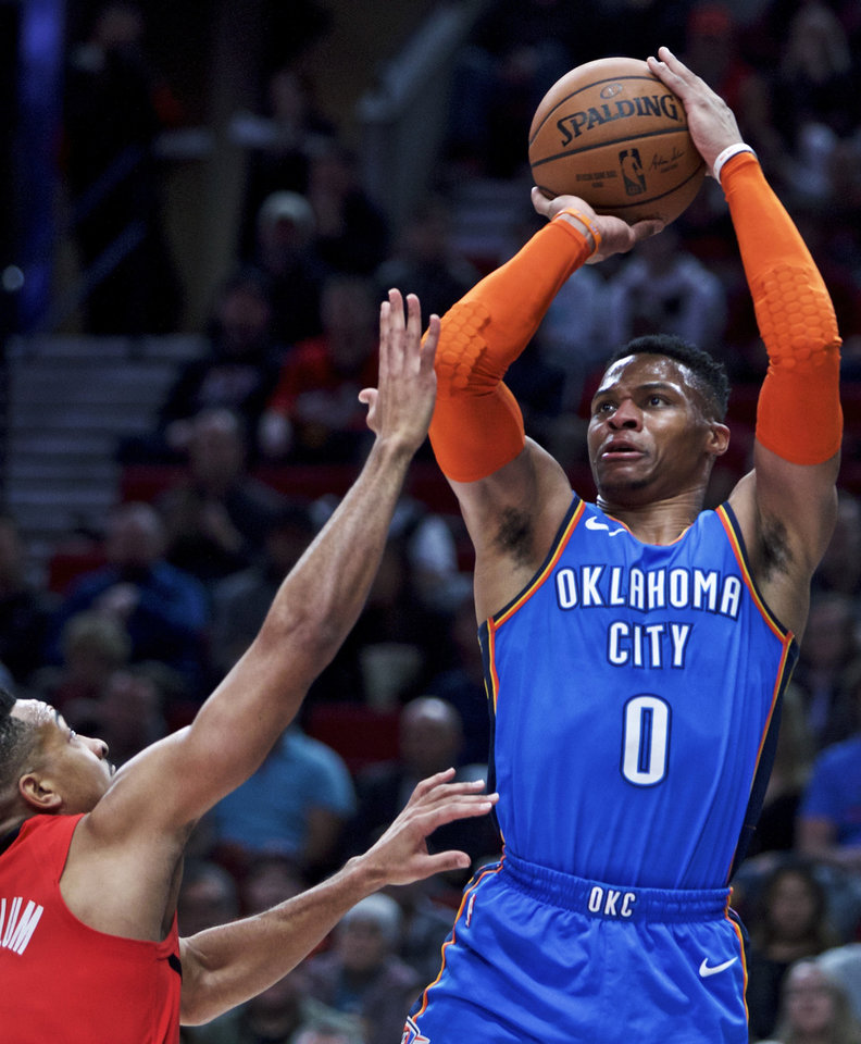 Photo - Oklahoma City Thunder guard Russell Westbrook, right, shoots over Portland Trail Blazers guard CJ McCollum during the first half of an NBA basketball game in Portland, Ore., Friday, Jan. 4, 2019. (AP Photo/Craig Mitchelldyer)