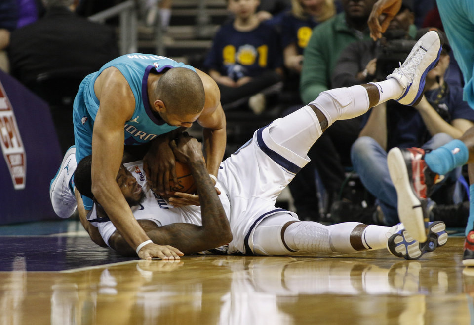 Photo - Charlotte Hornets forward Nicolas Batum (5), left, battles Memphis Grizzlies forward JaMychal Green for a loose ball in the first half of an NBA basketball game in Charlotte, N.C., Friday, Feb. 1, 2019. (AP Photo/Nell Redmond)