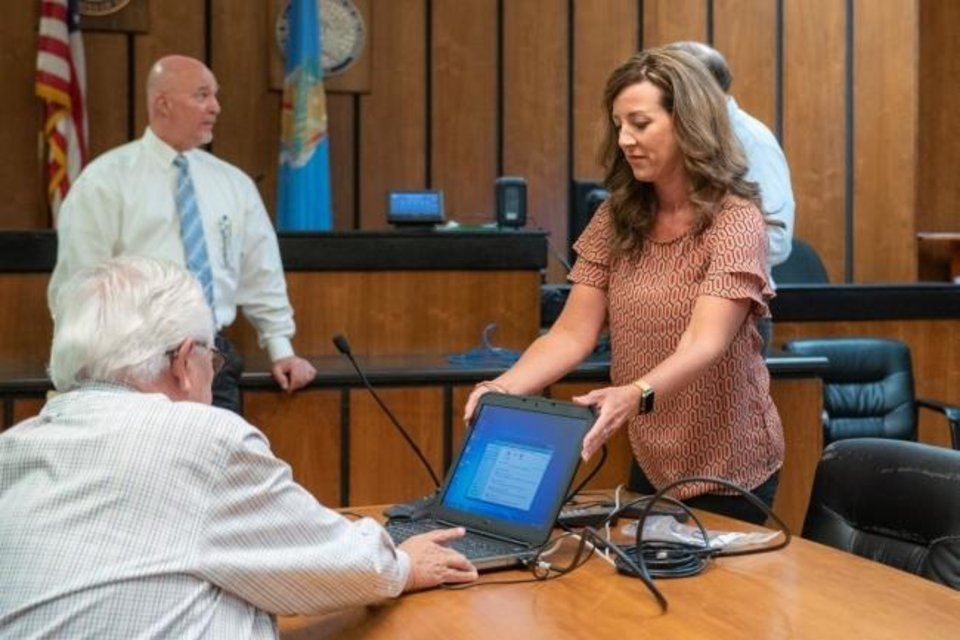 Photo -  McCurtain County Assistant District Attorney Emily Maxwell Herron, right, sets up a computer in a courtroom so a doctor can provide expert testimony by video. Advocates for domestic violence victims say the video testimony could also be used for protective order hearings. [Whitney Bryen/Oklahoma Watch]