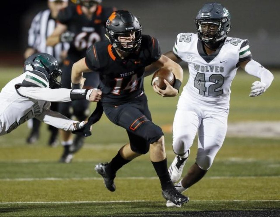Photo -  Norman's Cade Horton, center, runs from Edmond Santa Fe's Austin Roat, left, and Michael Pope last season. [Nate Billings/The Oklahoman]