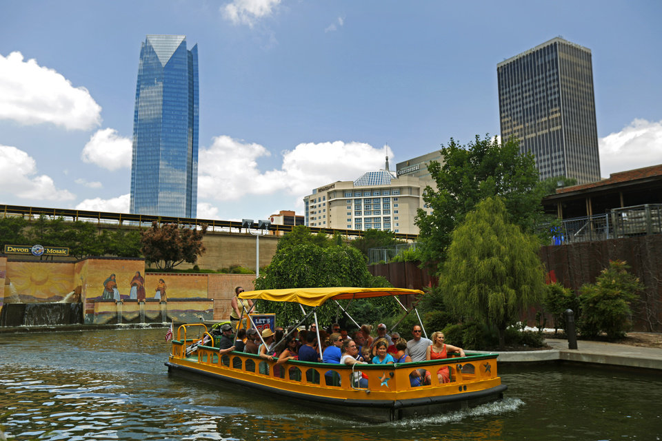 Photo -  A water taxi floats down the Bricktown Canal during the 2015 Rock the Boat festival along the canal in Oklahoma City. [Photo by Bryan Terry, The Oklahoman]