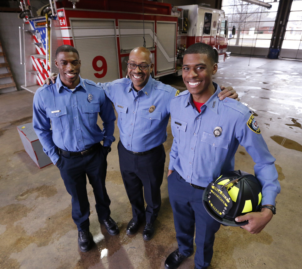 Photo -  Jack Baker poses with firefighter sons Javvero, left, and Malcolm at a south Oklahoma City fire station on Friday. [Photo by Steve Sisney, The Oklahoman]