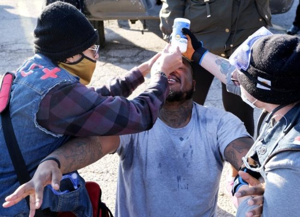 Photo -  Bystanders pour water on a man's face after police sprayed him with an irritant at the scene of a police shooting in northwest Oklahoma City. [Doug Hoke/The Oklahoman]