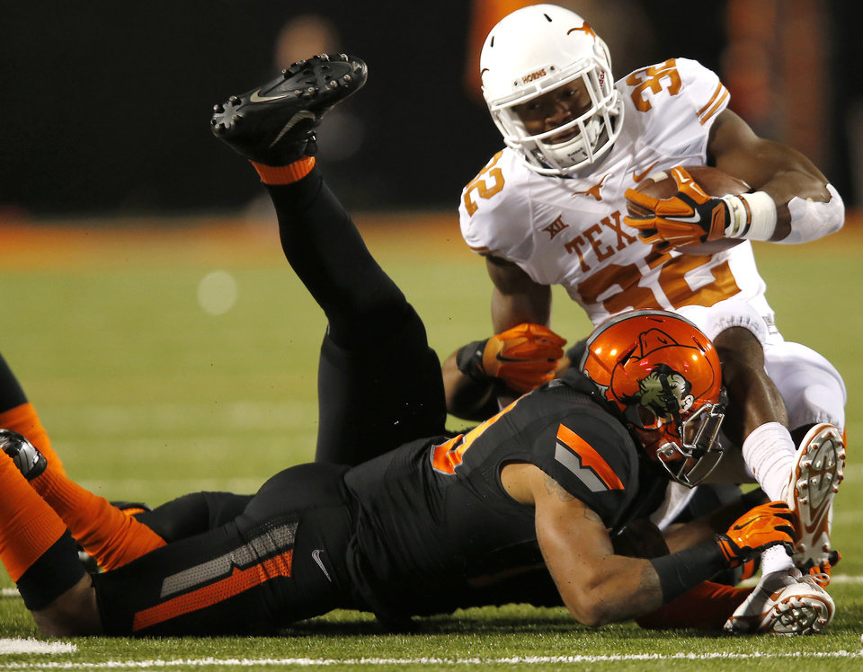 Photo - Texas' Johnathan Gray (32) is brought down by the Oklahoma State defense during the college football game between the Oklahoma State University Cowboys (OSU) the University of Texas Longhorns (UT) at Boone Pickens Staduim in Stillwater, Okla. on Saturday, Nov. 15, 2014.  Photo by Sarah Phipps, The Oklahoman