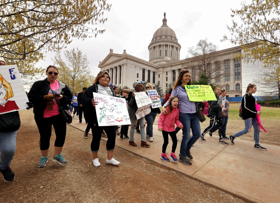 Photo -  Teachers, students and parents form a line around the building as they participate in a walkout at the Oklahoma State Capitol building on Thursday in Oklahoma City. [Photo by Steve Sisney, The Oklahoman]