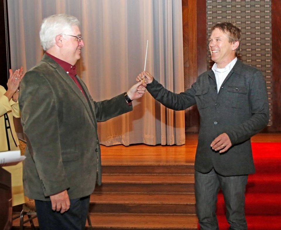 Photo - Oklahoma City Philharmonic music director Joel Levine, left, passes the conductor's baton to Alexander Mickelthwate, the philharmonic's music director designate during a ceremony Monday at the Civic Center Hall of Mirrors. Photo By Steve Gooch, The Oklahoman