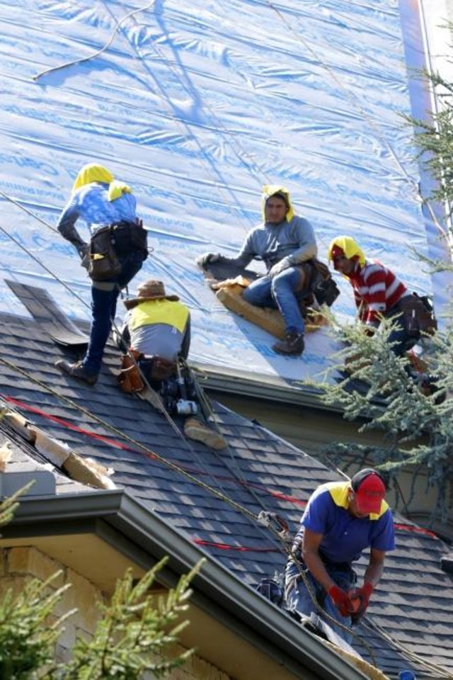 Photo -  Impact Construction Group workers install a Fortified roof. [DOUG HOKE/THE OKLAHOMAN]