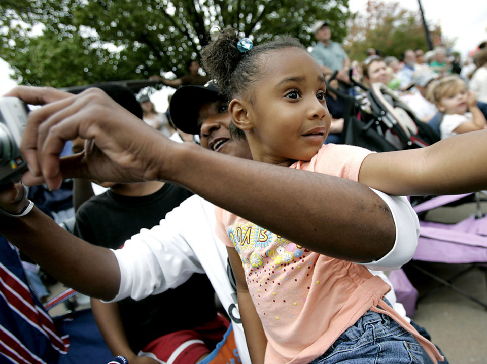 Photo - Jaida O'Conner, age 3, watches the parade while sitting in the arms of her grandmother, Toye Hamilton, of Oklahoma City, during the Oklahoma Centennial Parade in Oklahoma City on Sunday, Oct. 14, 2007. By John Clanton, The Oklahoman