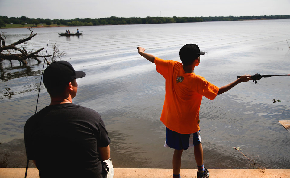 Photo -  A boy casts a line at Arcadia Lake. There are great opportunities now for bank fishing in the Oklahoma City area, and the city's annual