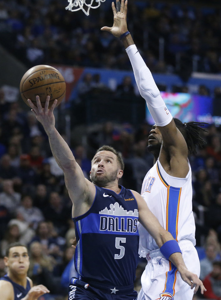 Photo - Dallas Mavericks guard J.J. Barea (5) goes up to shoot in front of Oklahoma City Thunder forward Nerlens Noel, right, in the first half of an NBA basketball game in Oklahoma City, Monday, Dec. 31, 2018. (AP Photo/Sue Ogrocki)