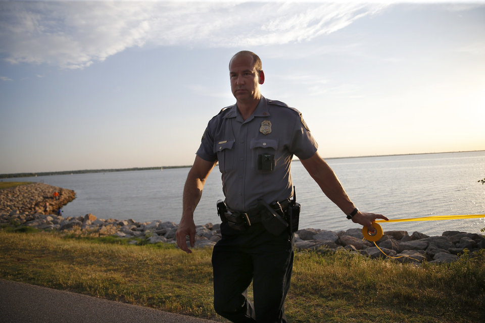 Photo - Police put up crime scene tape around the scene of a shooting on the east side of Lake Hefner in Oklahoma City, Thursday, May 24, 2018.  Photo by Sarah Phipps, The Oklahoman