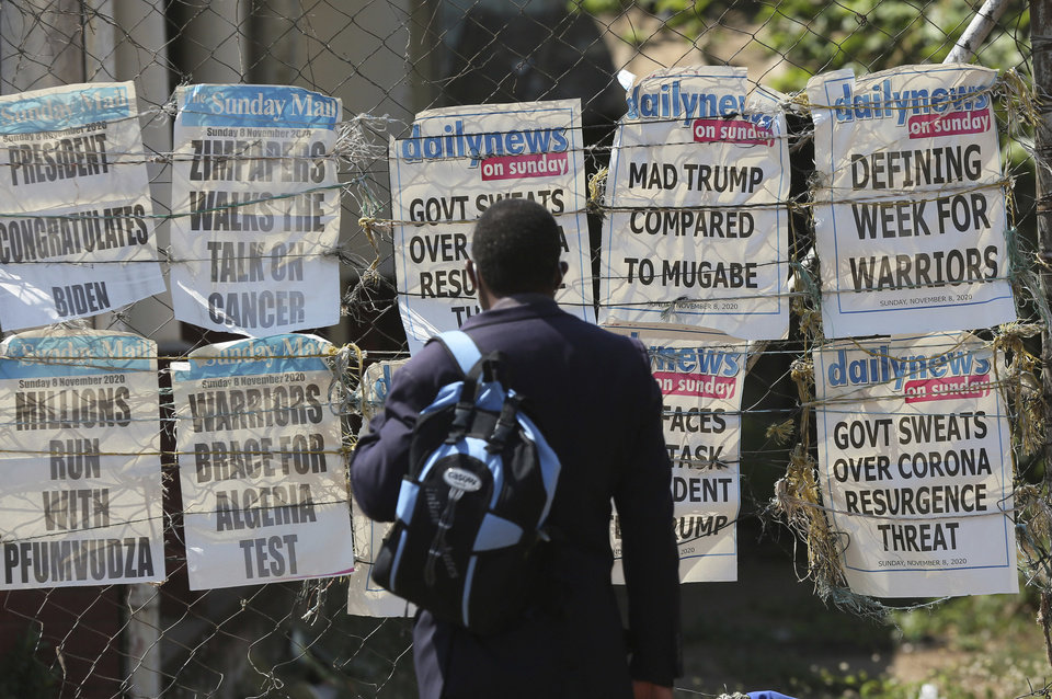 Photo -  A man reads newspaper headlines Sunday on a street of Harare, Zimbabwe. [Tsvangirayi Mukwazhi/the associated press]