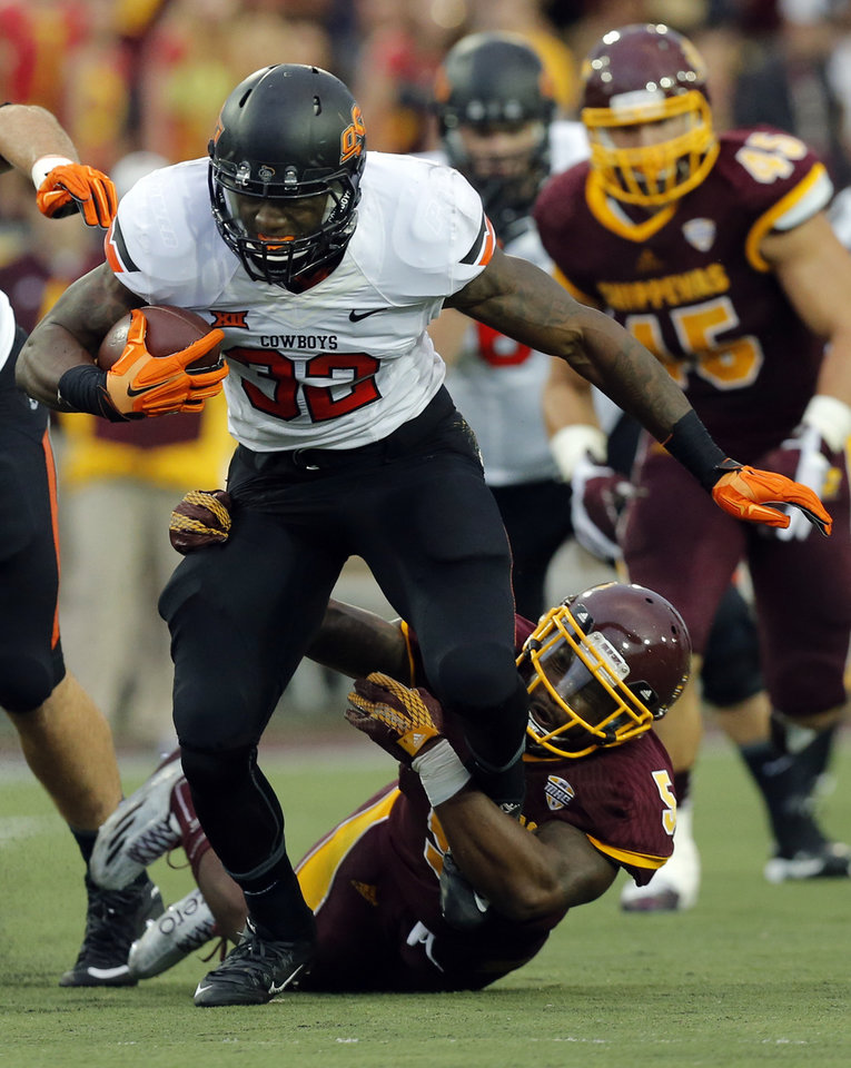 Photo - Oklahoma State's Chris Carson (32) tries to get by Central Michigan's Kavon Frazier (5) during the college football game between the Central Michigan Chippewas and the Oklahoma State University Cowboys at the Kelly/Shorts Stadium in Mount Pleasant, Mich., Thursday, Sept. 3, 2015. Photo by Sarah Phipps, The Oklahoman