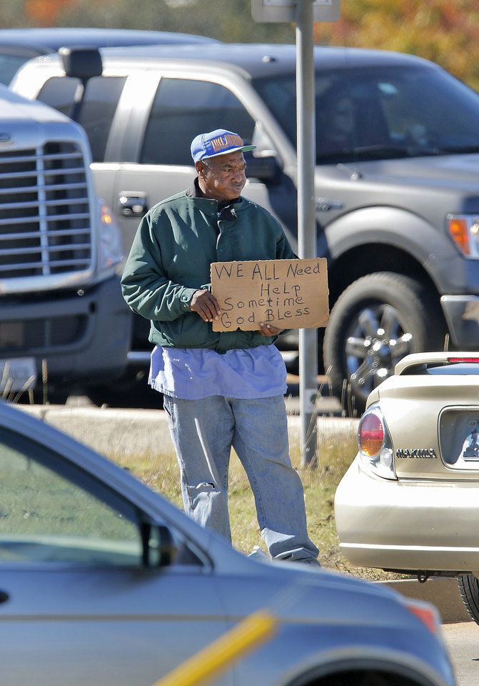 Photo -  A panhandler stands at the Memorial and May Avenue intersection looking for handouts in Oklahoma City, Friday October, 6 2015. Photo By Steve Gooch, The Oklahoman