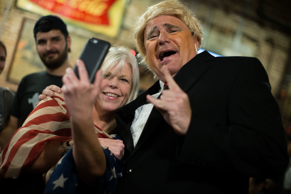 Photo - Hillary Clinton supporter Karen Benton, left, takes a selfie with Donald Trump impersonator RJ Morris at Manuel's Tavern before a presidential debate between Democratic presidential candidate Hillary Clinton and Republican presidential candidate Donald Trump, Monday, Sept. 26, 2016, in Atlanta. (AP Photo/Branden Camp)