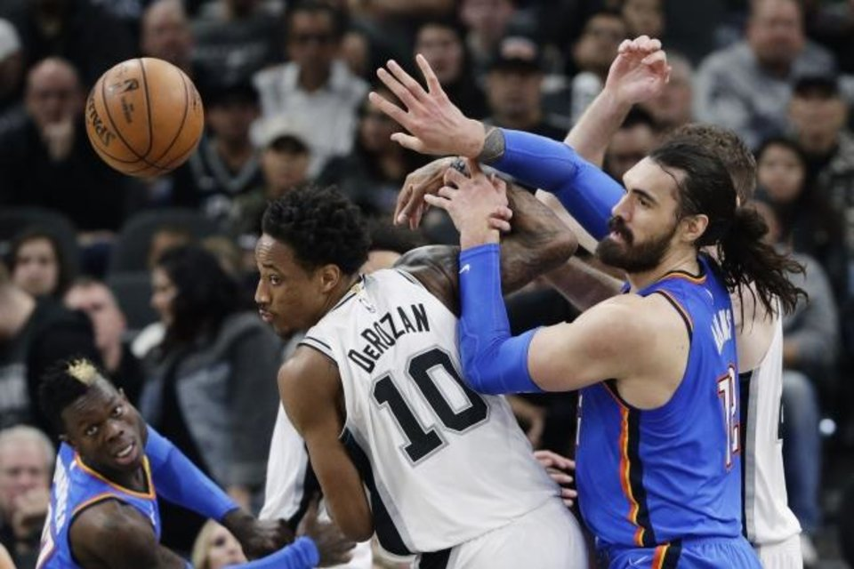 Photo -  San Antonio Spurs guard DeMar DeRozan and Oklahoma City Thunder center Steven Adams, right, scramble for a rebound during the second half of Thursday night's game in San Antonio. Oklahoma City won 109-103, its fourth consecutive victory. [AP Photo/Eric Gay]