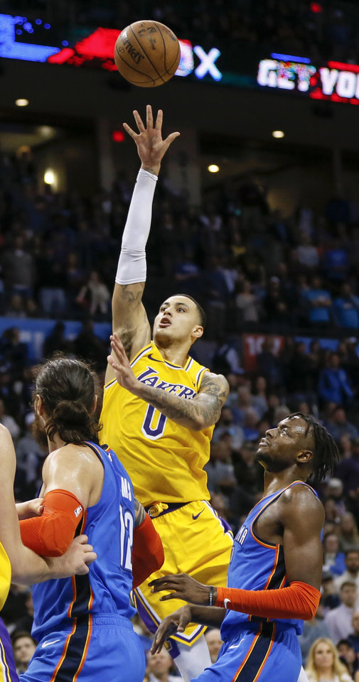 Photo - Los Angeles' Kyle Kuzma (0) takes a shot near Oklahoma City's Jerami Grant (9) and Steven Adams (12) in the fourth quarter during an NBA basketball game between the Los Angeles Lakers and the Oklahoma City Thunder at Chesapeake Energy Arena in Oklahoma City, Thursday, Jan. 17, 2019. Los Angeles won 128-138 in overtime. Photo by Nate Billings, The Oklahoman