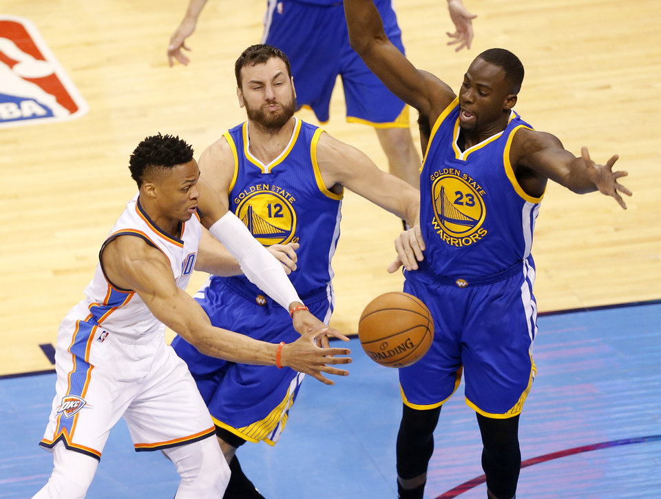 Photo - Oklahoma City's Russell Westbrook (0) passes the ball as Golden State's Andrew Bogut (12) and Draymond Green (23) defend during Game 3 of the Western Conference finals in the NBA playoffs between the Oklahoma City Thunder and the Golden State Warriors at Chesapeake Energy Arena in Oklahoma City, Sunday, May 22, 2016. Photo by Sarah Phipps, The Oklahoman
