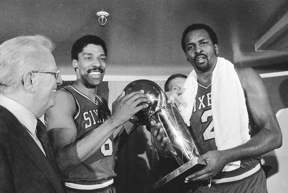 Photo -  Moses Malone, right, and Julius Erving celebrate after the Sixers won the 1983 NBA title. [AP photo]