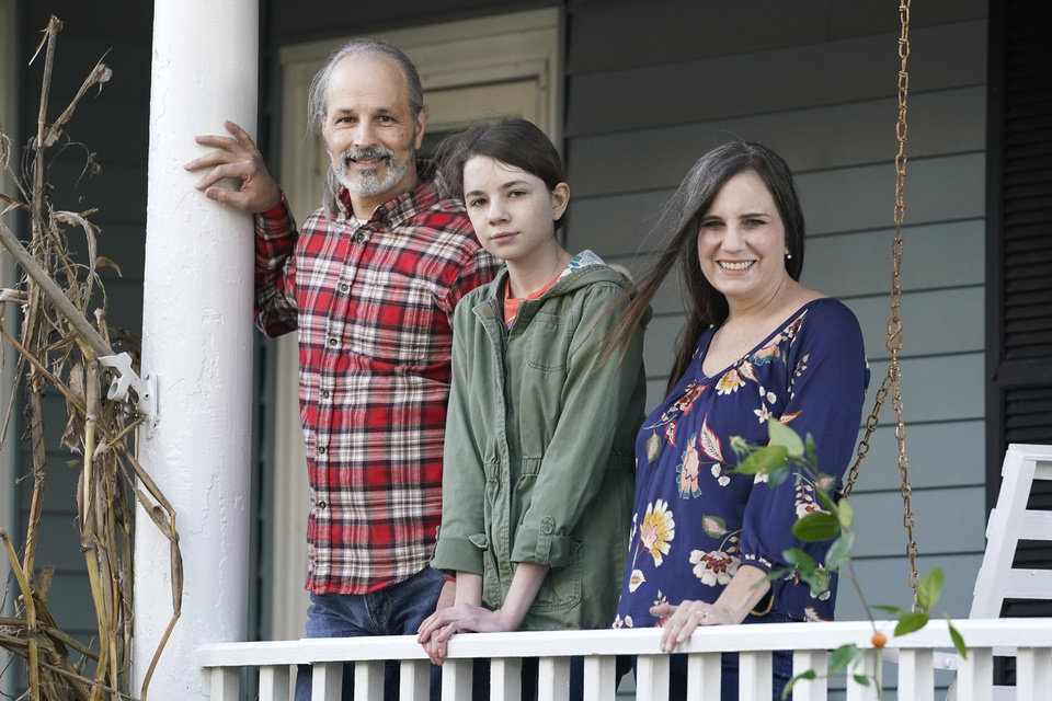 Photo -  Olivia Chaffin, center, stands for a portrait with her parents, Doug, left, and Kim Chaffin, at their home in Jonesborough, Tenn., on Nov. 1, 2020. Olivia, who stopped selling Girl Scout cookies because they contain palm oil says,