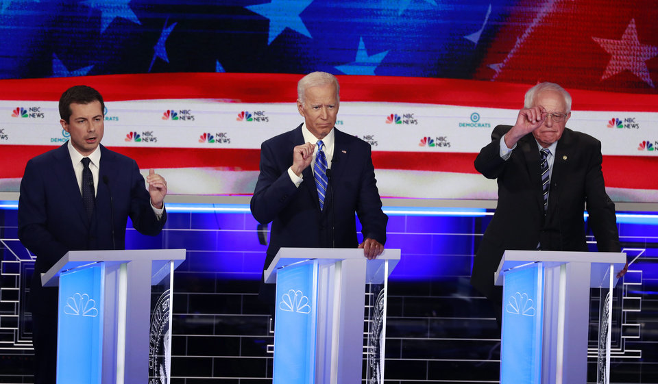 Photo - Democratic presidential candidate South Bend Mayor Pete Buttigieg, left, speaks as former vice president Joe Biden and Sen. Bernie Sanders, I-Vt., gesture, during the Democratic primary debate hosted by NBC News at the Adrienne Arsht Center for the Performing Art, Thursday, June 27, 2019, in Miami. (AP Photo/Wilfredo Lee)