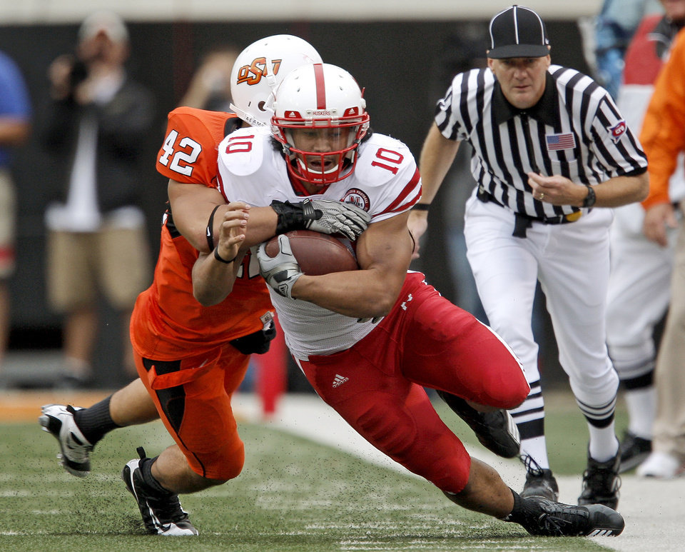 Photo - Nebraska's Roy Helu Jr. is brought down by OSU' Justin Gent during the college football game between the Oklahoma State Cowboys (OSU) and the Nebraska Huskers (NU) at Boone Pickens Stadium in Stillwater, Okla., Saturday, Oct. 23, 2010. Photo by Bryan Terry, The Oklahoman