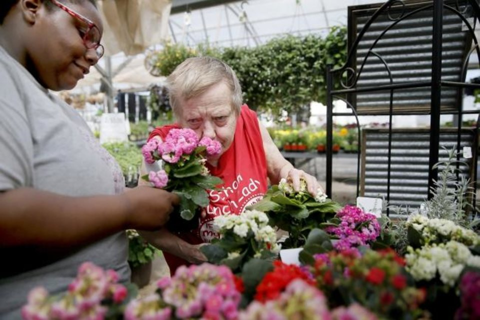 Photo -  Shay S. holds flowers out as Linda B. smells them at Kristy Lyn's Flowers & Gifts. [Bryan Terry/The Oklahoman]