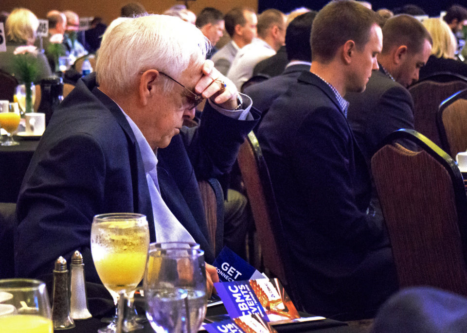 Photo - David Baker lowers his head in prayer during the CBMC Metro Prayer Breakfast at the Cox Convention Center in Oklahoma City, Okla. on Tuesday, April 16, 2019.   Photo by Chris Landsberger, The Oklahoman