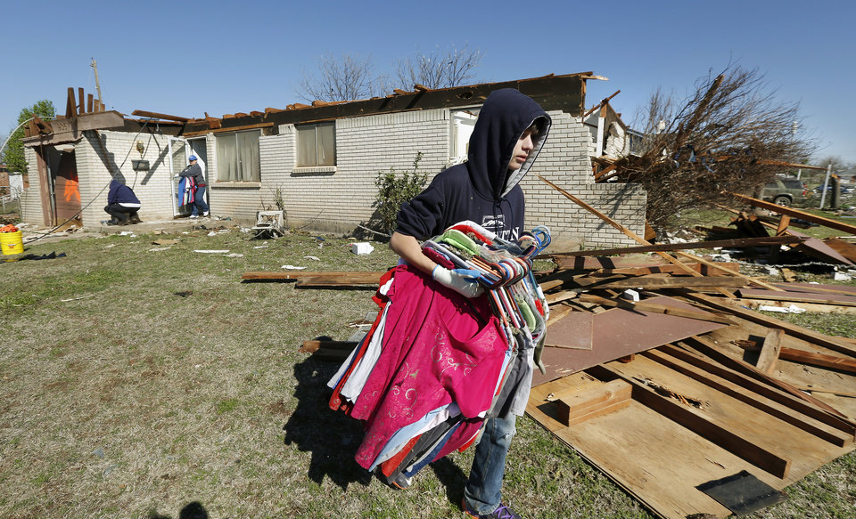Photo - Joetta Strain's grandson, Chase, carries some of his grandmother's clothes to a car so they can be salvaged from her tornado damaged home. The tornado ripped the roof from her house. Neighborhood  between NW 5 and Main Street, and between Telephone Rd. and Santa Fe in Moore.  Thursday morning, March 26, 2015, the day after a tornado damaged homes and a school Wednesday evening. Photo by Jim Beckel, The Oklahoman